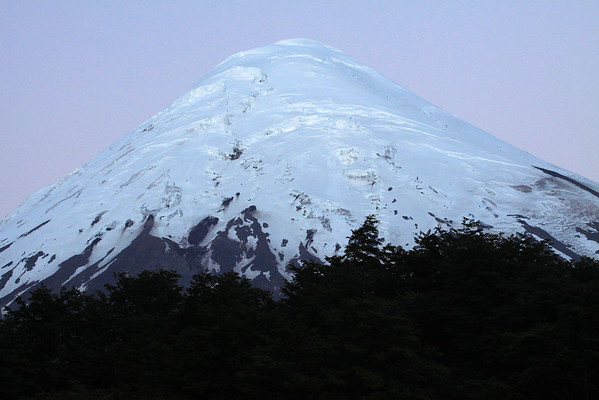 Twilight dawn glow, upon the the southeastern slope and glacial ice cap peak, of Volcan Osorno.