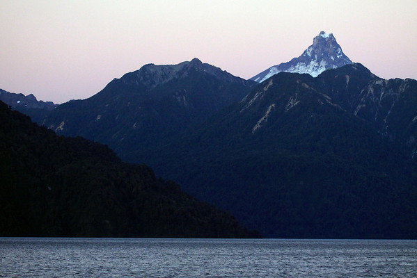 Twilight dusk light - across Lake All Saints - beyond the forested slopes, along the northern shoreline - to the glacial ice and igneous rock peak, of Volcan Puntiagudo.