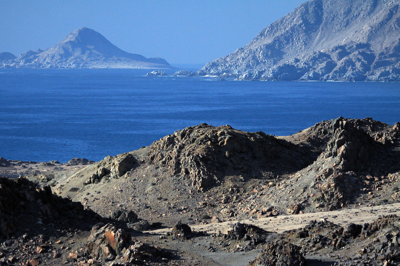 Across the rocky outcrops - beyond Cabo Falso Pande Azucar, the western slope of Cerro Castillo - out to Isla Pan de Azugar, rising to about 525 ft. (160 m), above the Pacific Ocean.