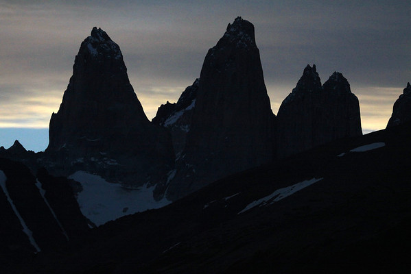 Near apparent sunset silhouette of the Towers of Paine - Torre Sur, with the glacier below and Cerro Fortaleza (distal, r) - Torre Central, adjacent to the twin peaks of Torre Norte - a slight glimpse of both Cerro Nido Condor (r) and Punta Negra (distal, l).