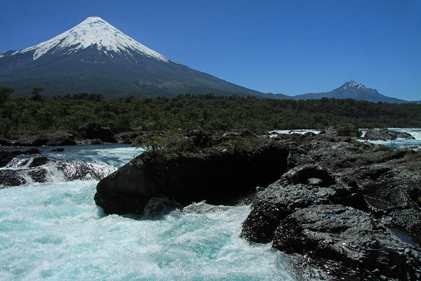 Up the Rio Petrohue, among the igneous rock - across the vegetated slopes of the Valdavian Temperate Rainforest ecoregion - to the glacial ice cone cap, of Volcan Osorno - and glacial ice streams upon Cerro Picada - under a naked Los Lagos region sky.