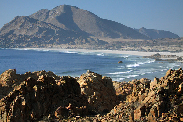 Beyond the rocky outcrops scattered with shrubs of the Atacama Desert - down to the waves braking upon the Playa Refugio - with Cerro Castillo (l) - and Cerro Soldado (beyond, r).