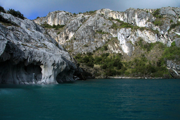 Western shoreline of Lago Carrera - revealing its water sculpted marble rock, along the glacial water, and Patagonia vegetation (tussock grass, shrubs, and southern beech trees) scattered among the marble outcrops.