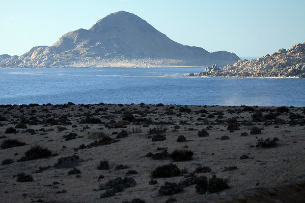 Beyond the shaded coastal desert vegetated bluff, and mist from the breaking waves (r) - past the sunlit rocky southwestern slope and tip of Cerro Soldado - out to Isla Pan de Azucar, and up its mostly shaded eastern slope, rising to the peak at about 525 ft. (160 m).