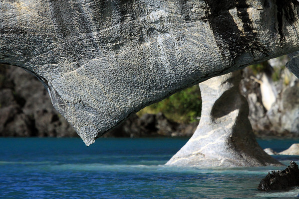 Beyond the marble overhang, displaying its scalloped or concave weather texture, that is streaked with manganese oxide leachate - to the base of a water eroded and sculpted spire, or sea stack - upon the glacial milk water of Lago Carrera.