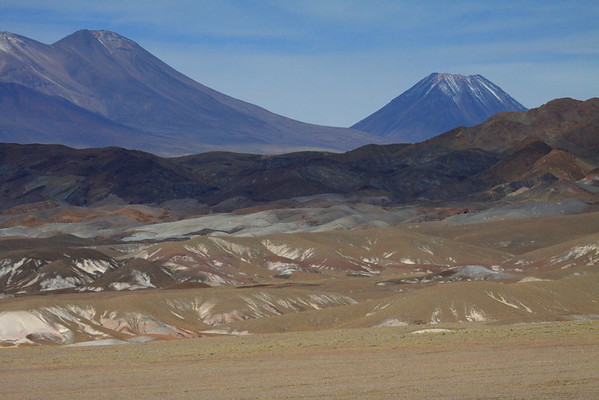 Across the mineral-stained southeastern slopes, from the Salar Atacama - up to the slope from Volcán Lejía (l) and beyond to Volcán Cenizas (r).