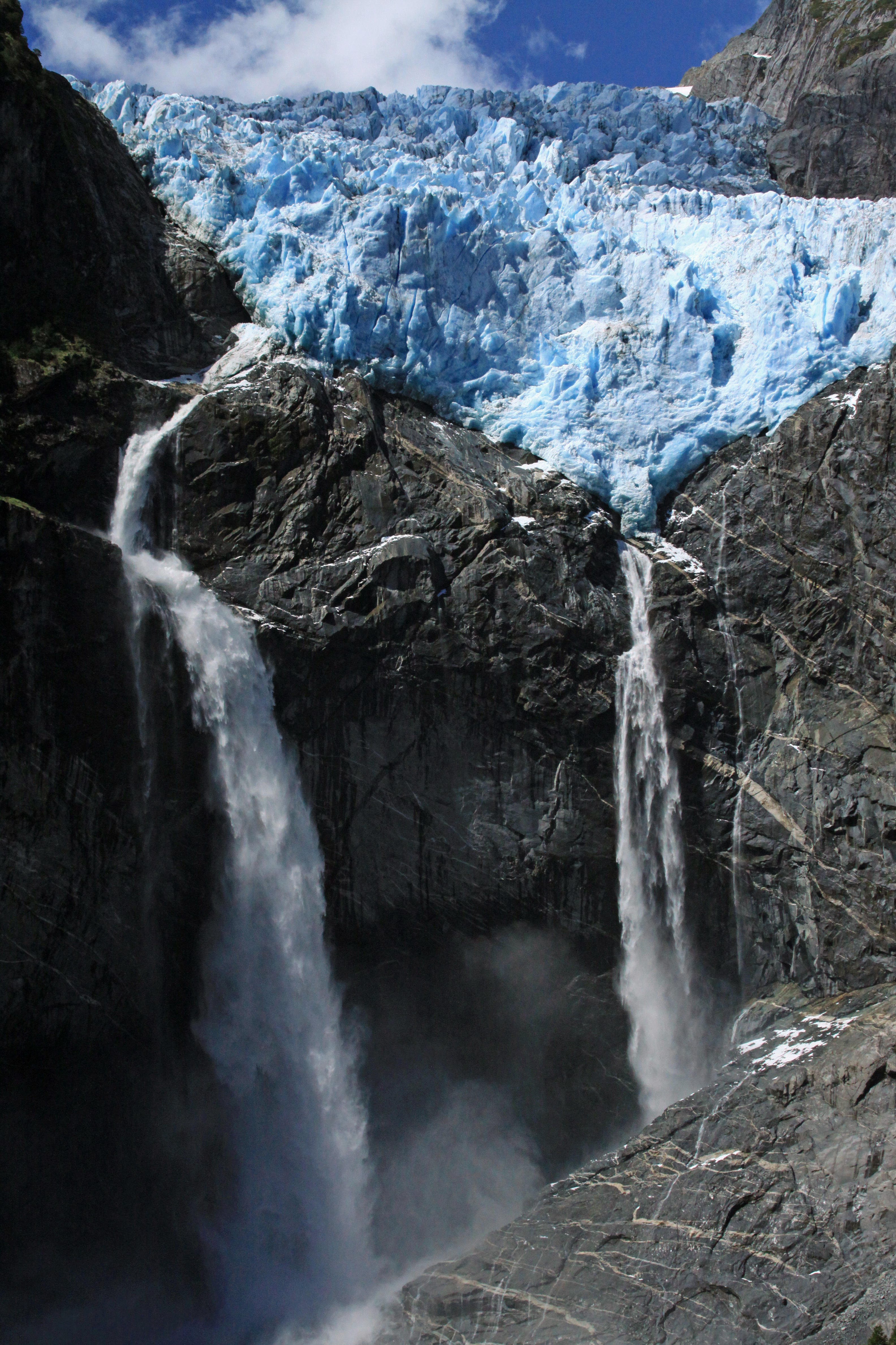 Beyond the igneous rock slope, to a pair of plunge falls and a cascade/ribbon falls, descending from the blue hue terminus snout ice, of the Ventisquero Colgante.