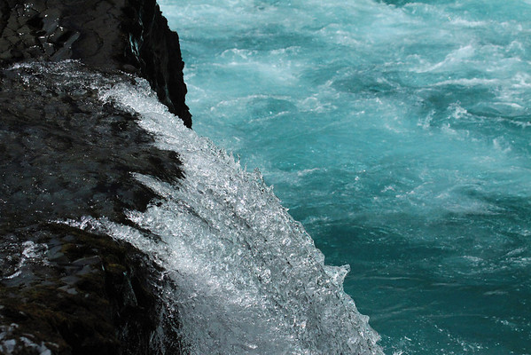 Over the igneous rock ledge, the crest water along the Petrohue Waterfalls.