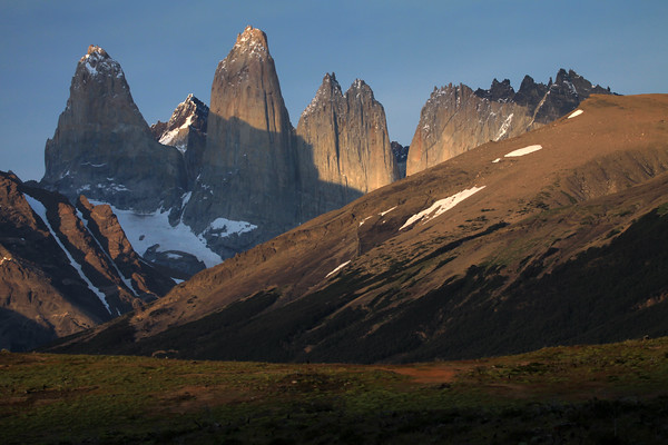 Morning sunlight upon the cushion plants - to the Lenga Beech forest along the lower slope of Cerro Paine (r) - and the glacial ice streams upon the slope of Mt. Almirante Nieto (l) - beyond to the Torre Sur, with Cerro Fortaleza beyond and the glacier below - the igneous granite spire of Torre Central, and twin peaks of Torre Norte - the sunlit jagged granite peak and lower hornfels ridge, of Cerro Nido Condor - and a slight glimpse of the distal, Cerro Escucio.