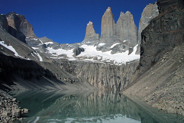 Across the placid glacial water reflection, to the Towers of Paine, with the glacier below, and its melt water streaks upon the rock slope - Cerro Nido Condor (r) - with the Mt. Almirante Nieto (l) - and distal view of Hoya (blade).