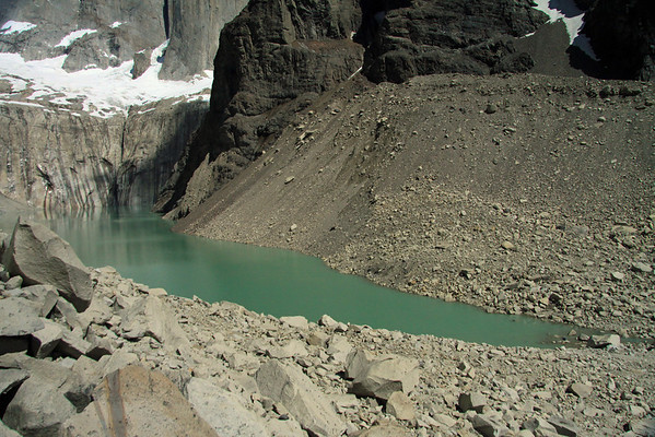 Beyond the granite till - down to the glacial milk or rock flour water lagoon, measuring about 1 mi. (1.6 km) long, and 1/2 mi. (.8 km) at its widest - with the glacier below the Torres del Paine distal - and the lower slope of Cerro Nido Condor (r).