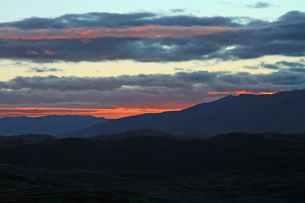 Twilight dawn glow (with apparent sunrise at near 5:37, here at about 51° S and 73° W), upon the distal horizon of Cerro Cazador (l) and Cerro Toro (r) - to Rio Asencio, part of the drainage basin, near its confluence with Lago Nordenskjold - Torres del Paine National Park.