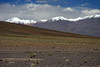 Along the southern slope of Cerro Puntilla, scattered with xerophytic shrubs and tussock grass, northern Antofagasta region of Chile - to Cerros Cañapa, rising to about 19,298 ft. (5,882 m), in the Potosi department of Bolivia, among the cumulus clouds.