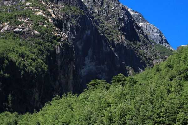 Sunlight and shadows upon the forested and rock slopes - Rio Simpson National Reserve - Aisen region, Coyhaique province.