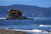 Beyond the sunlit sea stack, among the waves, along the southern shore of Bahia Cucao - to the distal eroded coastal slopes, of the Pirulil Mountains - western Isla Chiloé.