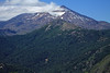 Over the peak of Cerro Mora - to the sunlight and cloud shadows upon the glacier, in the northwestern crater of Volcan Tolguaca - and the glacial formed and now forested lower slopes.
