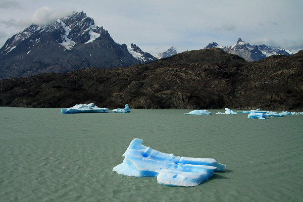 Drift ice upon the glacial flour/milk water of Lago Grey - across the vegetated and rocky peninsula - to Cerro Paine Grande (l) - next is Cerro Fortaleza (with its peak in the cloud) - then back to Cuernos del Paine (Norte, Principal, and Este) - with Mt. Almirante Nieto (distal, r).
