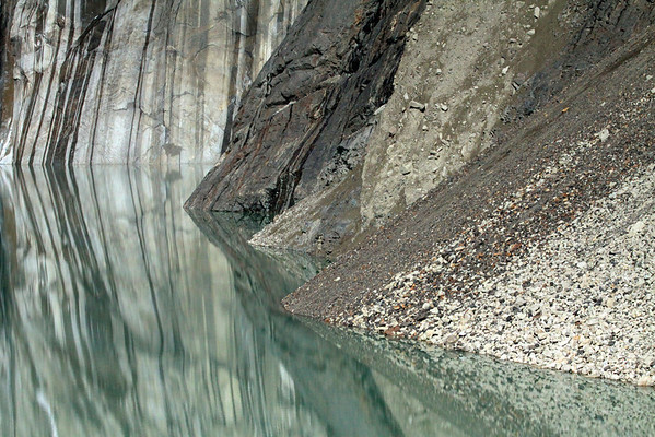 Reflection upon the placid glacial water lagoon, of the glacial sculpted rock, streaked with glacier melt water, during the early summer season - with the steep slope of Cerro Nido Condor (r) - and the fusion of glacial till, composed of igneous rock (light colored) and metamorphic rock.