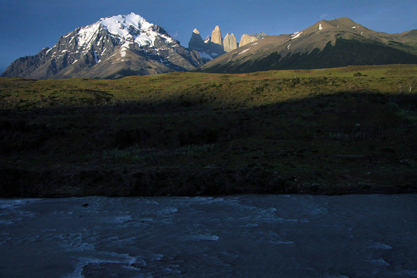Across the early morning shadowed Rio Paine - to  the sunlit Paine Massif or Cordillera Paine - Cerro Paine (r) and Mt. Almirante Nieto (l) - to the distal Torres del Paine - with Cerro Fortaleza, distal between Torre Sur and Torre Central - and Cerro Nido Condor, adjacent to the twin peaks of Torre Norte.
