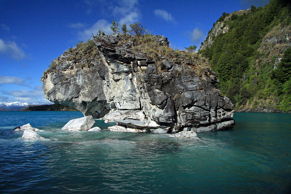 Beyond the eroded sea stack and adjacent marble outcrops and fallen boulder - to a partial view of Capilla de Marmol (Marble Chapel) - upon the glacial water of Lago Carrera - southwestward, to the distal glacial ice slopes of the Patagonia Andes.