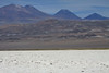 Across the Salar Atacama (salt plain) - the southwestern area of the Puna de Atacama (high altitude plateau of the Andes Mountains) - up to Volcán Lejía, peaking at around 19,006 ft  (5,793 m) - Volcán Chiliques (c), with its conical shape peak near 18,952 ft. (5,778 m) - and Volcán Cenizas (r), topping around 18,635 ft. (5,680 m) - Loa province, eastern Antofagasta region.