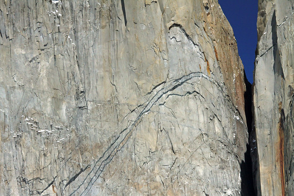 Glaciation sculpturing of plutonic igneous granite, revealing shadowed overhangs and snow covered ledges, along the vertical spire slope of Torre Norte - at the col with Cerro Nido Condor (r).