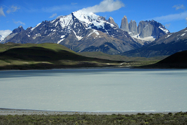 Westward view across Laguna Amarga - beyond the cloud-shaded slopes, across the mouth of the Valle Asencio, to Mt. Almirante Nieto (c) - Cuerno Principal (l) - and the Paine Towers (r), with the adjacent metamorphic rock capped Cerro Nido Condor.