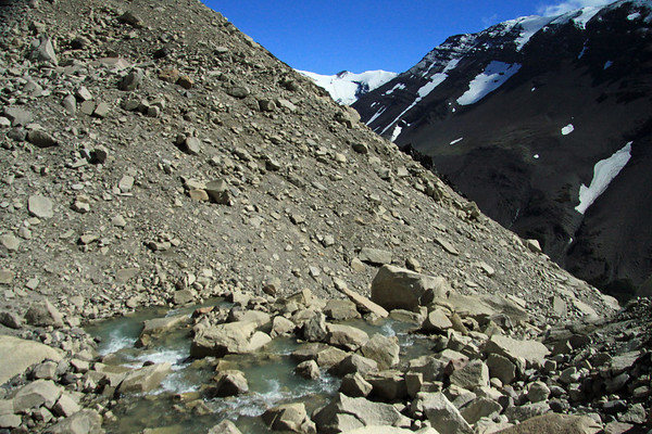 Down the glacial water flowing along the lateral moraine, and among the till - into the Asencio Valley below  - and to distal snow-cloaked slope and ridge of Cerro Koch.