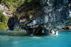 Capilla de Marmol - displaying is water eroded tunnel, arch, and overhangs - with the western shoreline of Lago Carrera, beyond and thru.