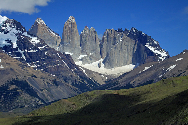 Ecological transition from the cloud-shaded slope of Patagonia Steppe ecoregion terrain (grasses and shrubs) - to the sunlit Magellanic Forest ecoregion (predominately southern beech trees) - here  viewing along the Valle Asencio - with the eastern slope of Mt. Almirante Nieto (l), beyond to the intrusive igneous granite Paine Towers, and adjacent hornfels rock capped Cerro Nido Condor - with the distal metamorphic rock capped Cerro Fortaleza (between Torre Sur and Central), and Cerro Escudo (between Cerro Norte and Cerro Nido Condor).