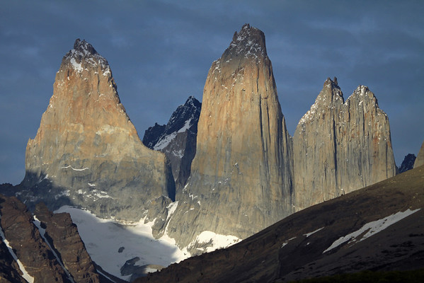 Beyond the partially sunlit slopes of Cerro Paine (r) and glacial ice stream slope of Mt. Almirante Nieto (l) - to the plutonic igneous granite peaks of the Torres del Paine, Torre Sur (with its peak slightly cloud-shadowed, also knows as D'Agostini), Torre Central (also with its peak cloud-shaded), and the sunlit twin peaks of Torre Norte - distal are the cloud-shaded Cerro Fortaleza (l) and glimpse of Cerro Escucio (r).
