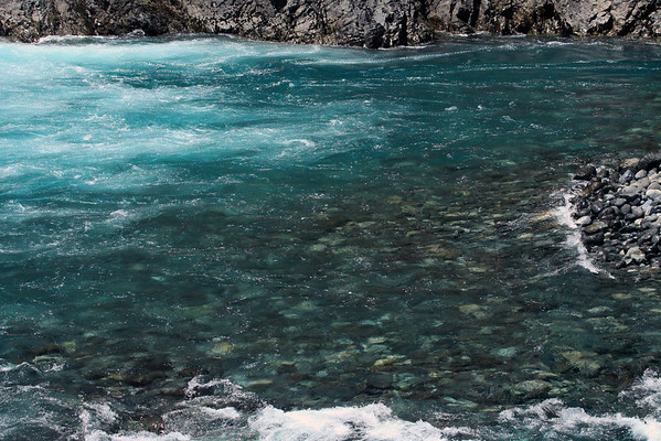 Turbulent glacial rock flour water, below the Petrohue Waterfalls, along the igneous rock cliff shoreline, with a wave upon the smooth water eroded glacial moraine.