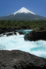 Igneous rock and glacial milk water, along the crest of the Petrohue Waterfall - to the distal glacier cone, atop the symmetrical stratovolcano - Volcan Osorno.