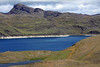 Lago Sarmiento - one of the largest endorheic lakes in all the Pagatonia area, that is not sourced by glacial ice, but by small streams - it measures about 15 mi. (24 km) long, and near 3.7 mi. (6 km) at its widest - here the narrow southern area, surrounded by Patagonia Steppe ecoregion vegetation (cushion plants, tussock grass, shrubs) and sedimentary rock - notice the minimally submersed rock in the main body of the water.