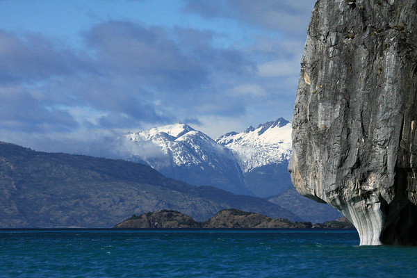 Southeastward beyond the sunlit metamorphic calcite marble, of Catedral Marmol - across the glacial water of Lago Carrera, and a rocky and vegetated island - to the distal glacial ice slopes, of the Patagonia Andes, among the cumulus clouds.