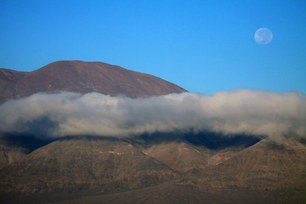 Beyond the cumulus cloud, to the peak of Cerro Moreno - and the waning gibbous moon.