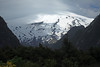 Beyond the rocky slopes cloaked with southern beech trees - to a patch of light beaming thru the clouds, and onto the northeastern slope of Volcan Villarrica, an active stratovolcano, with its summit in the clouds.