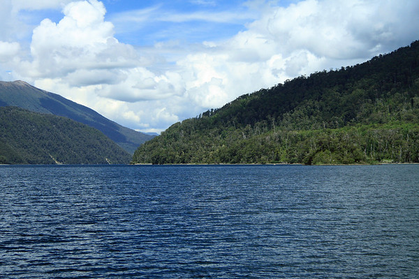 Lago Pirehueico - northwestward, along the sunlit and cloud-shadowed forested slopes, of the Valdavian Temperate Forest ecoregion.