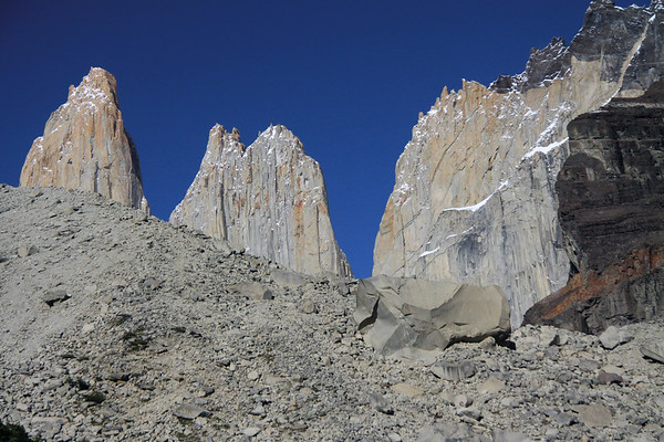 Across the moraine and glacial till, ranging from stones to 30 ft. (9 m) boulders - to Cerro Nido Condor (r), displaying its metamorphic rock cap - and Torres  Norte and Central, showing revealing a solid igneous rock spires and peaks.