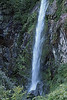 """A ribbon falls, descending among igneous rock and Valdavian vegetation - Portezuelo section of the Queulat National Park - Queulat, meaning """"sound of waterfalls"""", Chonos language."""