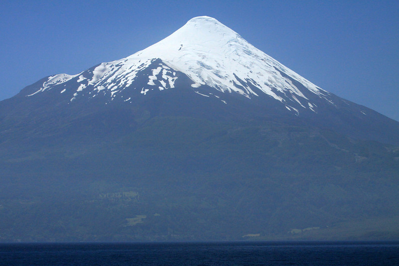 Across Lago Llanquihue - to the lower vegetated slopes and upper glacial ice peak, of the active Osorno Volcano - Los Lagos region.