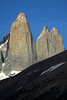 Torre Central attached to Torre Norte, by the col Bich (gap or saddle), both towers displaying its sunlit, glacial sculpted, plutonic igneous granite spires - with the northern lower buttress of Torre Sur (l), and between to the distal metamorphic caprock summit, of Cerro Fortaleza - foreground is the lower cloud-shadowed slope of Cerro Paine.