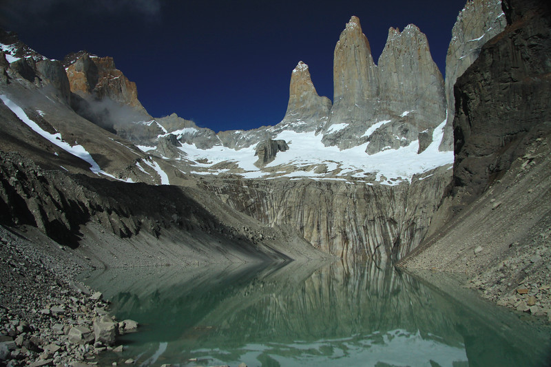 Reflection upon the glacial milk or rock flour water, of the base of Torres del Paine - with Cerro Nido Condor (r), revealing its lower slope and upper ridge - and Mt. Almirante Nieto (l), displaying its western upper slopes and ridge - and Hoya, blade, (distal, c).