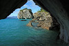 From the shaded entrance, to a marble sea cave - to the metamorphic calcite rock island or sea stack, of Catedral de Marmol, topped with vegetation - and the distal southeastern shoreline of Lago Carrera, and Patagonia Andes.