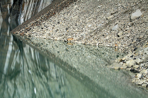 The calm water of the glacial milk or rock flour - reflecting the glacial till, waterfall, and glacier melt water streaks, upon the glacial sculpted rock- Torres del Paine.