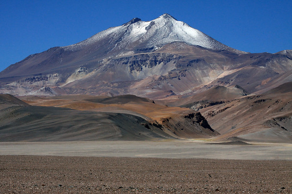 Volcan Copiapo, also called Volcan Azufre (sulfur) - a stratovolcano of extrusive igneous, volcanic rock - displaying its twin peaks, with the northern most (r), peaking at around 19,856 ft. (6,052 m) - this volcano separates the two sectors of the Nevado Tres Cruces National Park, from here along the Salar de Maricunga, with Laguna Negro Francisco.