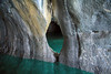 Water eroded marble arch, along the entrance to a sea cave, among the glacial milk water of Lago Carrera.