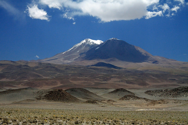 Across the xerophytic scrub vegetation of the endorheic basin and igneous rock outcrops, in the northern Antofagasta region - up to  the cloud-shaded southeastern slope, and sunlit peak of Volcan Aucanquilcha - Alto Loa National Reserve.