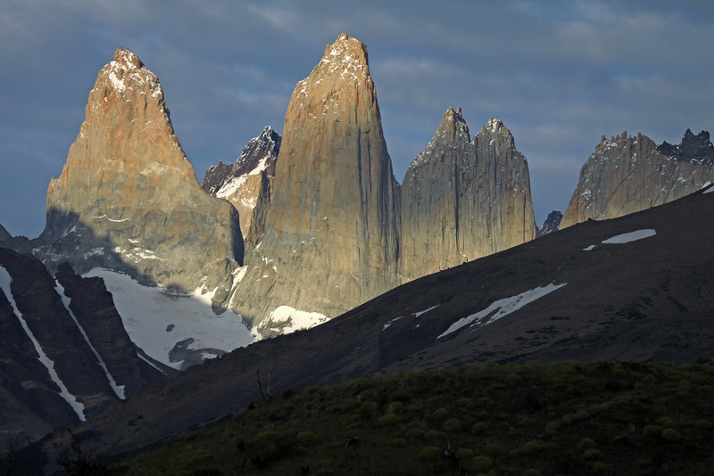 Early morning sunlight and shadows upon the Towers of Paine - Torre Sur (l), with the shadow of Mt. Almirante Nieto along its granite base, and adjacent to the glacier - beyond Sur's shaded northern buttress, to the metamorphic caprock of Cerro Fortaleza - Torre Central, and the adjacent cloud-shadowed twin peaks of Cerro Norte - between the gap with Cerro Nido Condor (r), displaying its cloud-shaded jagged granite peak, and lower hornfels ridge, to the distal Cerro Escucio peak - foreground beyond the cushion plants, are the shaded slopes of Cerro Paine (r) and Mt. Almirante Nieto (l), displaying its glacial ice streams.