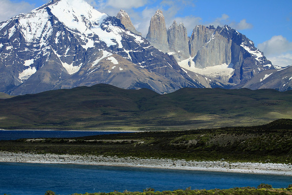 The rocky and calcium rich shoreline of Lago Sarmiento - across the mostly cloud shaded terrain of the Patagonia Steppe ecoregion - to Mt. Almirante Nieto (l) - Towers of Paine (r), with Cerro Nido Condor adjacent.